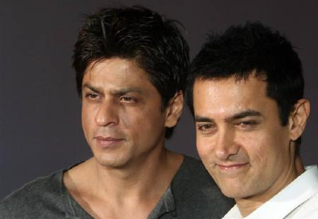 Bollywood actors and producers Shah Rukh Khan (L) and Aamir Khan pose for photographers after a news conference in Mumbai April 7, 2009. REUTERS/Punit Paranjpe