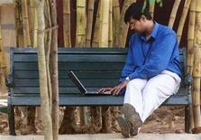 <p>n dipendente della società tech Infosys Technologies mentre lavora su una panchina con un laptop. SK/PB</p>
