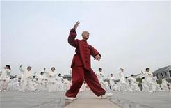<p>A man leads participants to perform Taiji, a traditional form of Chinese martial arts, in Liu'an, Anhui province July 13, 2008. REUTERS/China Daily</p>