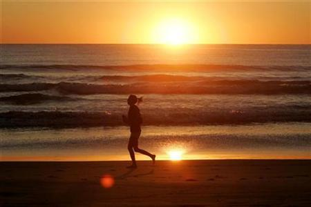 A jogger runs along the shore of Manly Beach after sunrise on the first day of Spring in Sydney September 1, 2008. REUTERS/Will Burgess