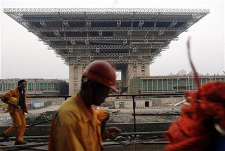 Migrant construction workers walk next to the Chinese Pavilion of Shanghai World Expo 2010 as they finish their working shift in the site in Shanghai April 15, 2009. REUTERS/ Nir Elias