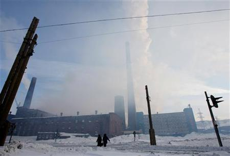 People walk near a nickel mine in the arctic city of Norilsk April 3, 2007. REUTERS/Denis Sinyakov