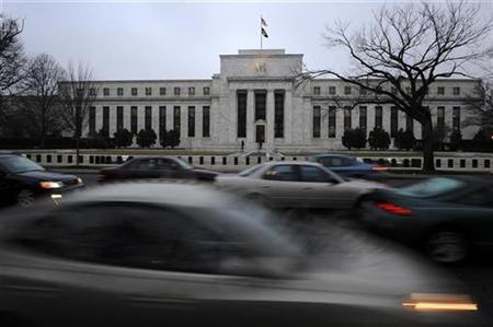 Morning commuters drive past the Federal Reserve Bank building in Washington March 18, 2009. REUTERS/Jonathan Ernst