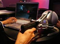 <p>A visitor plays a video game using a pistol grip accessory during the 2008 E3 Media & Business Summit in Los Angeles July 16, 2008. REUTERS/Mario Anzuoni</p>