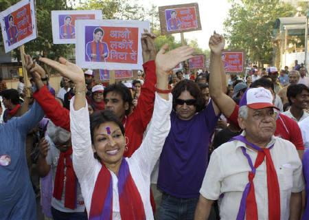 Dancer Mallika Sarabhai gestures as Bollywood actor Om Puri (R) accompanies her during an election campaign road show in Ahmedabad April 11, 2009, file photo. REUTERS/Amit Dave
