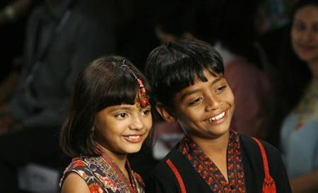 Azharuddin Ismail and Rubina Ali (L), actors in the film ''Slumdog Millionaire'', display outfits designed by Ashima Leena during a fashion show on the second day of India Fashion Week in New Delhi March 19, 2009. REUTERS/Adnan Abidi