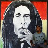 <p>A man sits by a mural of Jamaican reggae master Bob Marley in Kingston July 12, 2001. REUTERS/Kimberly White</p>