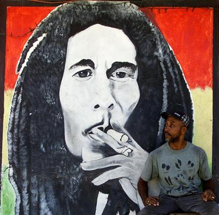 A man sits by a mural of Jamaican reggae master Bob Marley in Kingston July 12, 2001. REUTERS/Kimberly White