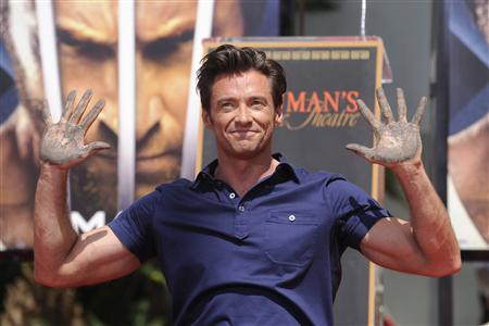 Hugh Jackman shows the cement on his hands during a ceremony where the actor places his hand and foot prints in cement in front of the Grauman's Chinese Theater in Hollywood April 21, 2009. REUTERS/Phil McCarten