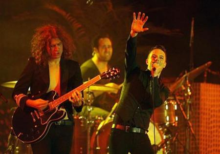 Vocalist Brandon Flowers (R), guitarist Dave Keuning (L) and drummer Ronnie Vannucci Jr. of The Killers perform at the Coachella Music Festival in Indio, California April 18, 2009. REUTERS/Mario Anzuoni