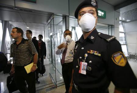 4月27日、アジア通貨は豚インフルエンザへの懸念でマレーシアリンギ主導で下落。写真はクアラルンプール空港で米国からの乗客をチェックする警察当局者(2009年 ロイター/Bazuki Muhammad)