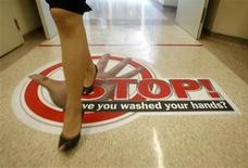 <p>A staff member walks over a sign reminding staff to wash their hands as a precaution when leaving wards at a hospital in Singapore April 27, 2009. Countries around the world have moved to contain the spread of a possible pandemic after a new swine flu outbreak killed 103 people in Mexico. Twenty cases have been identified in the United States and six in Canada, with no deaths reported. REUTERS/Vivek Prakash</p>