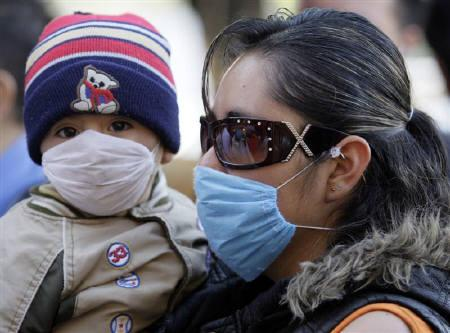 A mother and her son wear protective masks in Mexico City April 28, 2009. REUTERS/Daniel Aguilar
