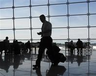 <p>A man checks his phone as he makes his way to a flight in a file photo. REUTERS/Mike Blake</p>