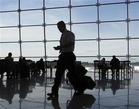 A man checks his phone as he makes his way to a flight in a file photo. REUTERS/Mike Blake