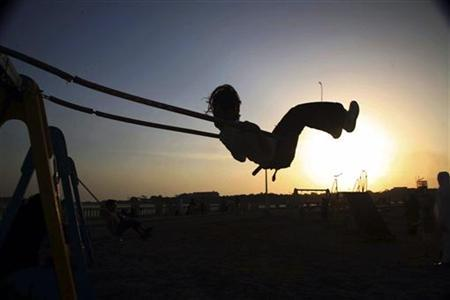 A child plays on the swings and is silhouetted along a beach overlooking the Red Sea in Jeddah in this file photo from July 21, 2007. REUTERS/Susan Baaghil