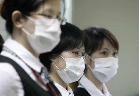 Airport staff wearing face masks monitor for signs of fever among passengers at Songshan Airport in Taipei, May 2, 2009. REUTERS/Pichi Chuang