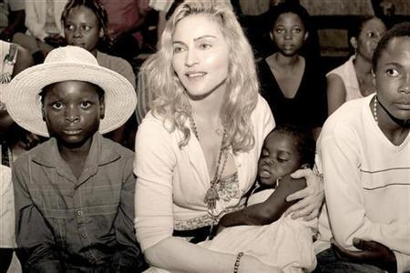 Madonna holds the child named Mercy, whom she hopes to adopt, in this undated publicity photo taken in Malawi and released to Reuters April 13, 2009. REUTERS/Tom Munro/Warner Brothers Records/Handout