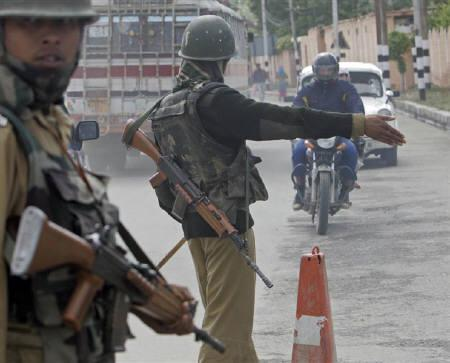 Policeman stops traffic at a security barricade during a strike in Srinagar May 6, 2009. REUTERS/Fayaz Kabli