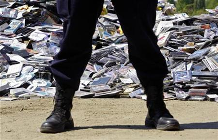 A policeman guards about 168,000 pirated CDs and DVDs with music, films and softwares seized from street sellers and shops in the biggest action against intellectual property piracy in Bucharest April 23, 2009. REUTERS/Bogdan Cristel
