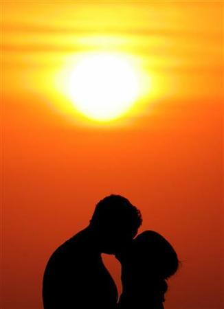 Western tourists kiss during sunset near Kuta beach on the Indonesian resort island of Bali, May 28, 2005. REUTERS/Darren Whiteside