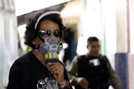 5月12日、世界保健機関が新型インフルが強毒性ウイルスに変異する可能性を指摘。写真はマスクをするパナマの露天商(2009年 ロイター/Alberto Lowe)