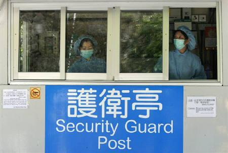 Health officers work inside a guard post at a closed camp where passengers are quarantined in Hong Kong May 7, 2009. Hong Kong  confirmed on Wednesday its second case of the new H1N1 flu strain, a man who had just returned from the United States. REUTERS/Bobby Yip