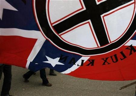 Members of a white supremacist group march under a Ku Klux Klan flag in Jena, Louisiana January 21, 2008. REUTERS/Jessica Rinaldi