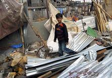 """<p>Azharuddin Ismail, ator de """"Quem Quer Ser Um Milionário"""", caminha sobre os escombros de sua casa demolida em Mumbai. 14/05/2009. REUTERS/Stringer</p>"""