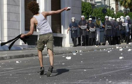 A Muslim immigrant throws a stone towards riot policemen during clashes after a rally in Athens May 22, 2009. REUTERS/John Kolesidis