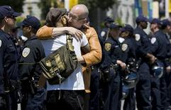 <p>A same sex couple hug in front of a line of police before being arrested for blocking the streets in a civil disobedience act in San Francisco, California, May 26, 2009. REUTERS/Kimberly White</p>