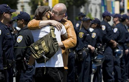 A same sex couple hug in front of a line of police before being arrested for blocking the streets in a civil disobedience act in San Francisco, California, May 26, 2009. REUTERS/Kimberly White