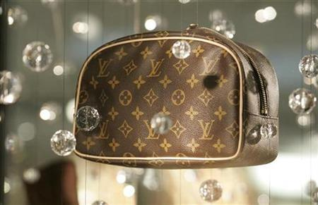 A luxury leather bag hangs on display in the window of a Louis Vuitton store as shoppers buy gifts on Christmas Eve at the Beverly Center shopping mall in Los Angeles, California December 24, 2008. REUTERS/Fred Prouser