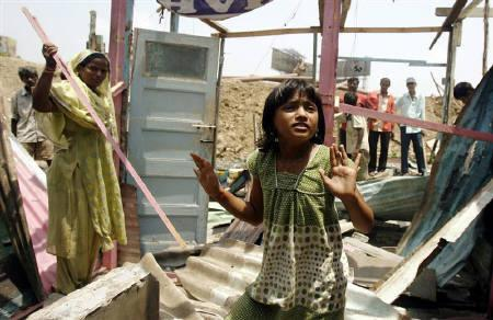 Rubina Ali (C), who acted as young Latika in the Oscar-winning movie ''Slumdog Millionaire'', looks around as her house gets demolished by local authorities, at a slum area in Mumbai May 20, 2009.  REUTERS/Punit Paranjpe