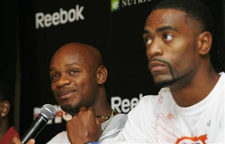Asafa Powell (L), former 100-meter world record holder from Jamaica, shows his lucky charm necklace as Tyson Gay, American record-holder at 100-meters, looks on during the Reebok Grand Prix athletics meet news conference in New York May 28, 2009. REUTERS/Shannon Stapleton
