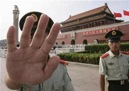 A paramilitary police officer gestures towards a photographer to stop taking pictures, while clearing tourists from Tiananmen Square in Beijing August 8, 2007. REUTERS/Stringer