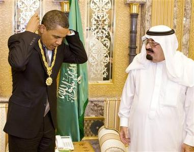 President Barack Obama receives a gift from Saudi Arabia's King Abdullah during a meeting at the king's farm outside Riyadh June 3, 2009. REUTERS/Larry Downing