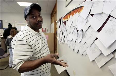 Unemployed truck driver Allen Askew III gestures to the photographer while checking job listings at a jobs search agency in Detroit, Michigan April 3, 2009. REUTERS/Rebecca Cook