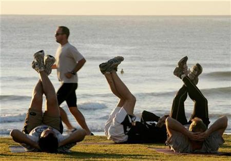 A jogger (2nd L) passes fitness enthusiasts performing stretching exercises after sunrise at Queenscliff Beach in Sydney on the first day of Spring September 1, 2008. REUTERS/Will Burgess