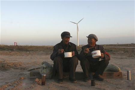 Workers eat their meals near a windmill at a wind power construction site in Wuzhong county, northwest China's Ningxia Hui Autonomous Region, October 19, 2007.REUTERS/Stringer