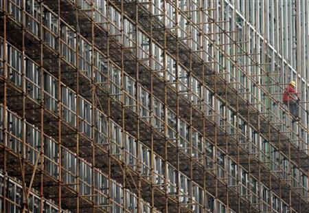 A worker builds up scaffolding at a construction site in Shanghai June 3, 2009. REUTERS/Stringer