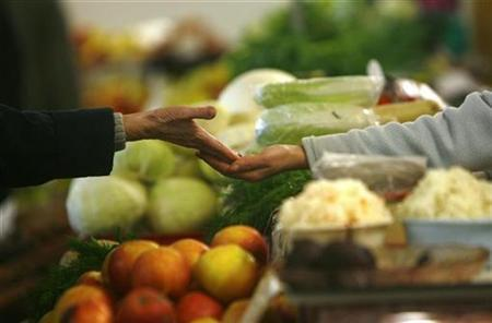 A customer pays after buying produce at a market in Riga February 19, 2009. REUTERS/Ints Kalnins