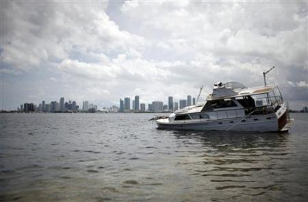 An partially submerged abandoned boat is seen in Miami Bay, June 9, 2009. According to a report from the Florida Fish & Wildlife Conservation Commission published in local media, there were 750 abandoned boats in the state in 2005 and that number has now increased to about 1500 as a result of the bad economy and hurricanes. REUTERS/Carlos Barria