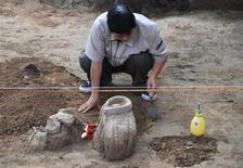 <p>Una arqueóloga desentierra a una estatua de terracota en un museo en Xi'an, China, 13 jun 2009. Un grupo de arqueólogos chinos reinició, 20 años después de empezados, los trabajos de excavación en el yacimiento del famoso ejército de terracota, dotados con tecnología que preservará los colores originales de las esculturas de 2.000 años de antigüedad. REUTERS/China Daily</p>