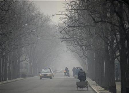 Cars and tricycles can be seen along a road on a hazy day in central Beijing March 4, 2009. REUTERS/David Gray