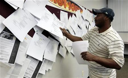 Unemployed truck driver Allen Askew III checks for job listings at a jobs search agency in Detroit, Michigan in this file image from April 3, 2009. REUTERS/Rebecca Cook/Files