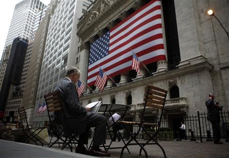 A man reads outside the New York Stock Exchange June 23, 2009. REUTERS/Eric Thayer