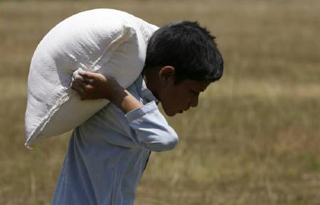 A boy carries a bag of flour after receiving military handouts of food and toys in Daggar, Buner district, about 220 km (137 miles) northwest of Islamabad, June 23, 2009.   REUTERS/Akhtar Soomro