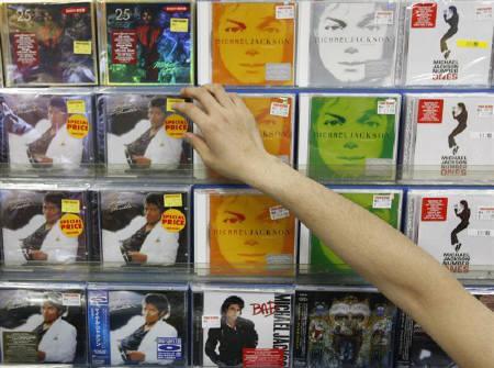 6月25日、米オンライン小売大手アマゾン・ドット・コムではマイケル・ジャクソンさんのアルバムへの注文が殺到。写真は東京都内のショップでジャクソンさんのCDに手を伸ばすスタッフ(2009年 ロイター/Kim Kyung-Hoon)