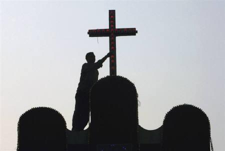 A worker works on the roof of a church ahead of Christmas in Siliguri in this December 23, 2007 file photo. REUTERS/Rupak De Chowdhuri/Files